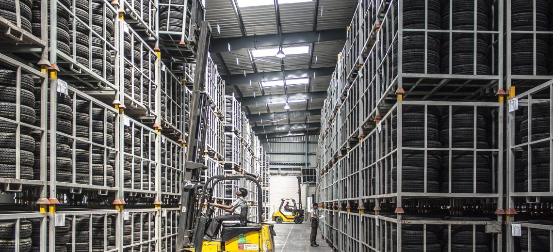 A worker using a semi electric pallet stacker within the warehouse environment.
